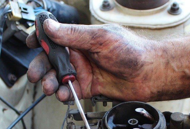 eine dreckige Hand mit Schraubenzieher repariert einen Turboschaden