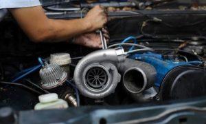 Ein Mann baut einen Turbolader ein