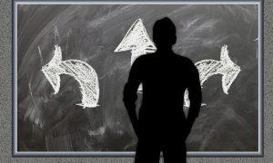 ein Mann steht vor einer Tafel mit drei Optionen